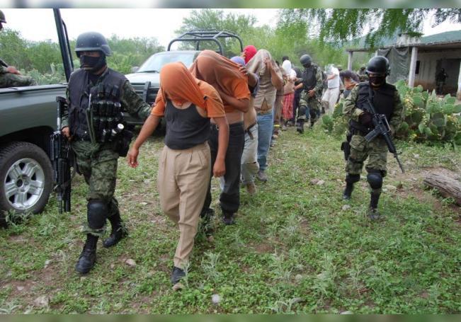 """Soldados del ejército mexicano custodian el martes 27 de abril de 2010, a las 16 personas que al parecer habían sido secuestradas por sicarios de """"Los Zetas"""", en un rancho en el municipio de Sabinas Hidalgo, Nuevo León (México). EFE/Juan Cedillo/Archivo"""