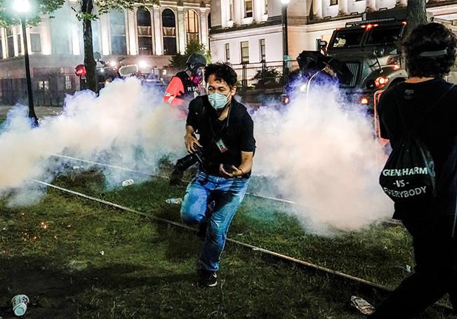 Un fotógrafo corre a ponerse a cubierto mientras la policía lanza gas lacrimógeno durante la tercera noche de disturbios en Kenosha, Wisconsin.
