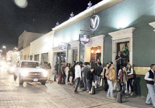 Un nutrido grupo de personas esperando entrar a uno de los bares más populares del centro de la ciudad.