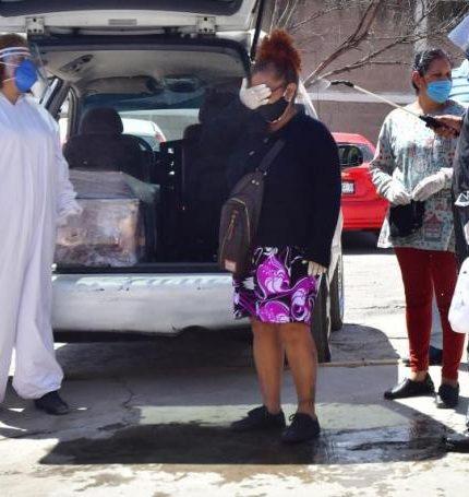 Fotografía fechada el 2 de julio de 2020 que muestra trabajadores funerarios mientras desinfectan a familiares de personas fallecidas por COVID-19, antes de ingresar al entierro en el panteón de San Isidro, en el municipio de Ecatepec (México). EFE/Jorge Núñez/Archivo