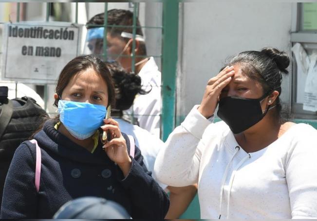 Familiares de personas afectadas por COVID-19 permanecen a las afueras de un hospital en espera de información, el 2 de julio de 2020, en Ciudad de México (México). EFE/ Jorge Núñez