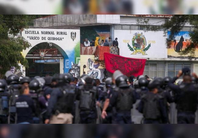 Estudiantes normalistas se resguardan en las instalaciones de su escuelas tras un enfrentamiento con policías, hoy en el occidental estado de Michoacán (México). EFE/Ivan Villanueva