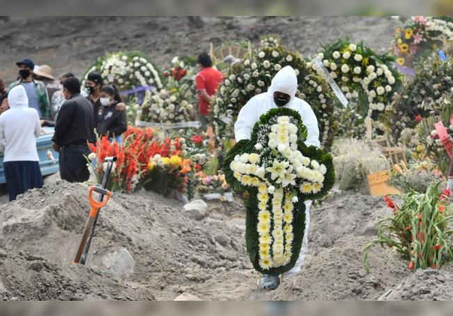 Fotografía fechada el 28 de Mayo de 2020 que muestra a un trabajador municipal colocando una cruz sobre una nueva tumba, en el terregoso panteón del municipio de Valle de Chalco (México). EFE/Jorge Núñez/Archivo