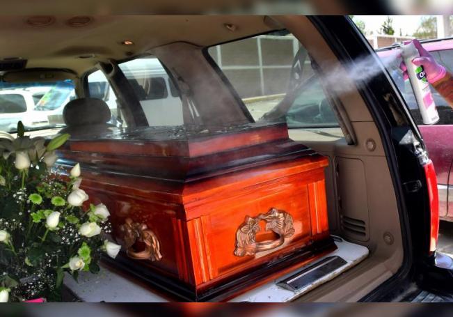 Un empleado funerario desinfecta un féretro cuya persona habría fallecido por COVID-19, el 2 de agosto de 2020 en Ciudad de México (México). EFE/Jorge Núñez/Archivo