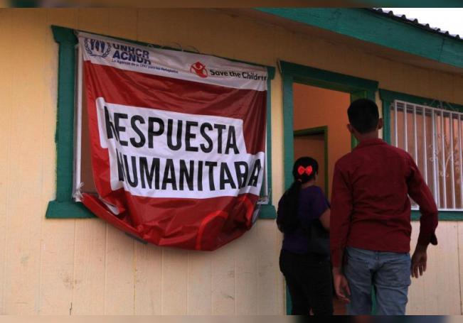 Migrantes caminan frente a un letrero en un albergue el 19 de septiembre de 2020 en Ciudad Juárez (México). EFE/Luis Torres