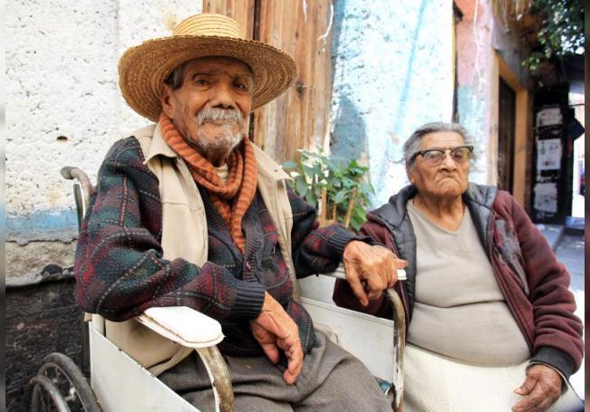 Fotografía que muestra a una pareja de personas de la tercera edad a las afueras de su domicilio en Ciudad de México (México). EFE Mario Guzman/Archivo
